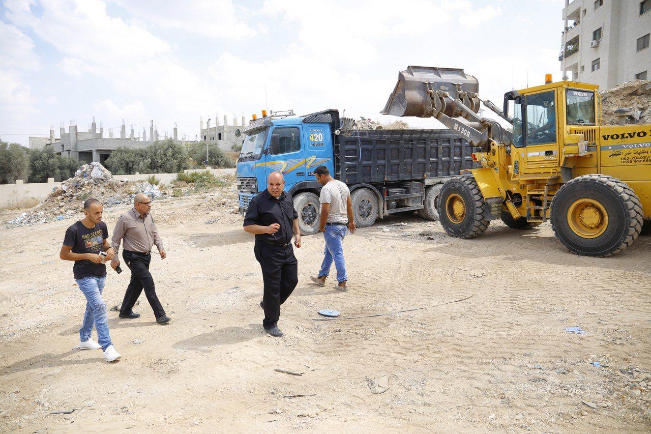 البلدية تباشر بأعمال نقل وترحيل مخلفات الابنية من الارض المنوي ا